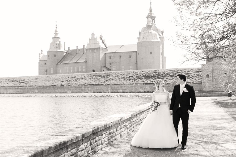 Brudpar som går framför Kalmar slott - bröllopsfotograf Phia Bergdahl Västervik