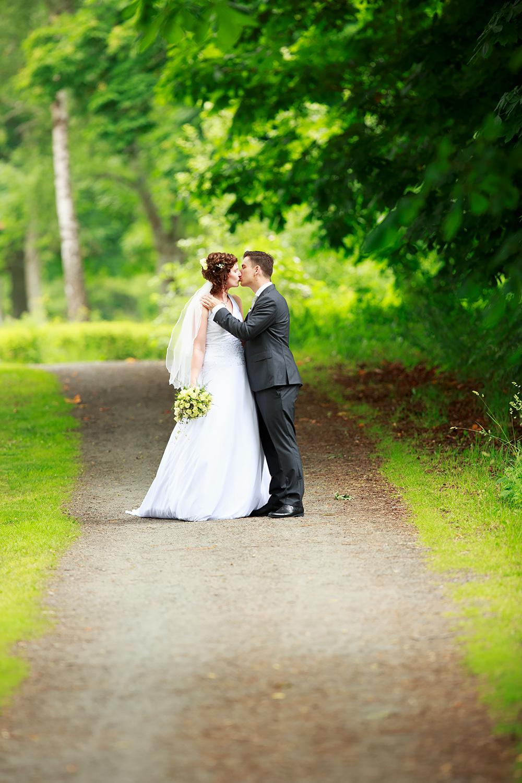 Brudpar som pussas i allé Gränsö slott fotograferad av bröllopsfotograf Phia Bergdahl Västervik