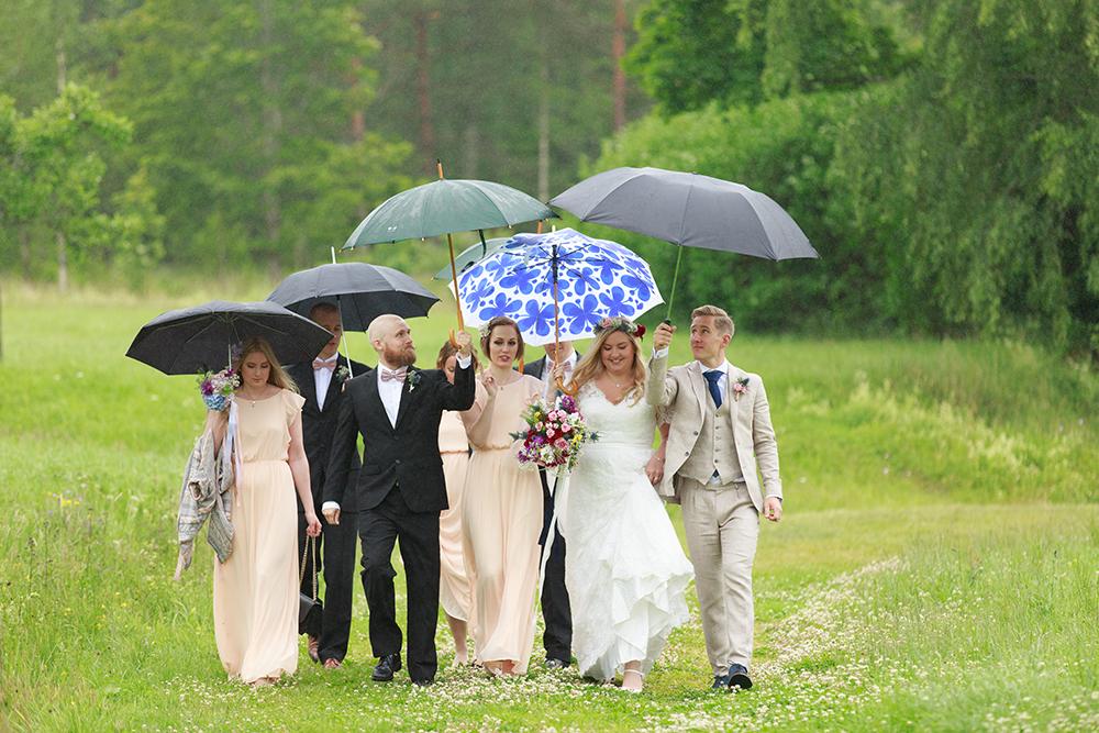 Brudfölje med paraplyer i äppellunden Västervik