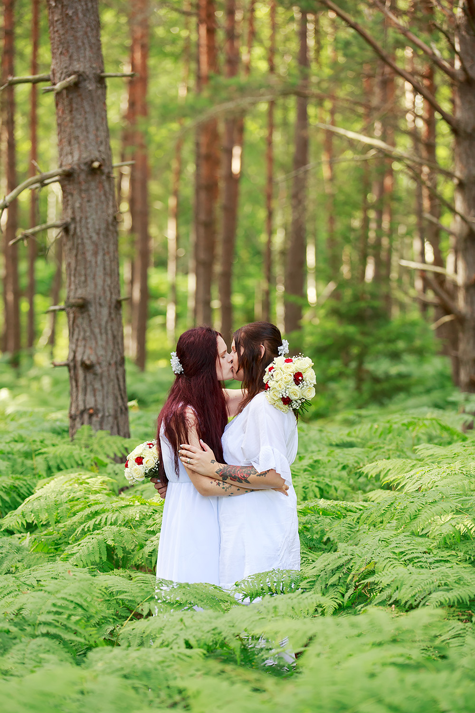 Brudar som kysser varandra i skogen på Gränsö