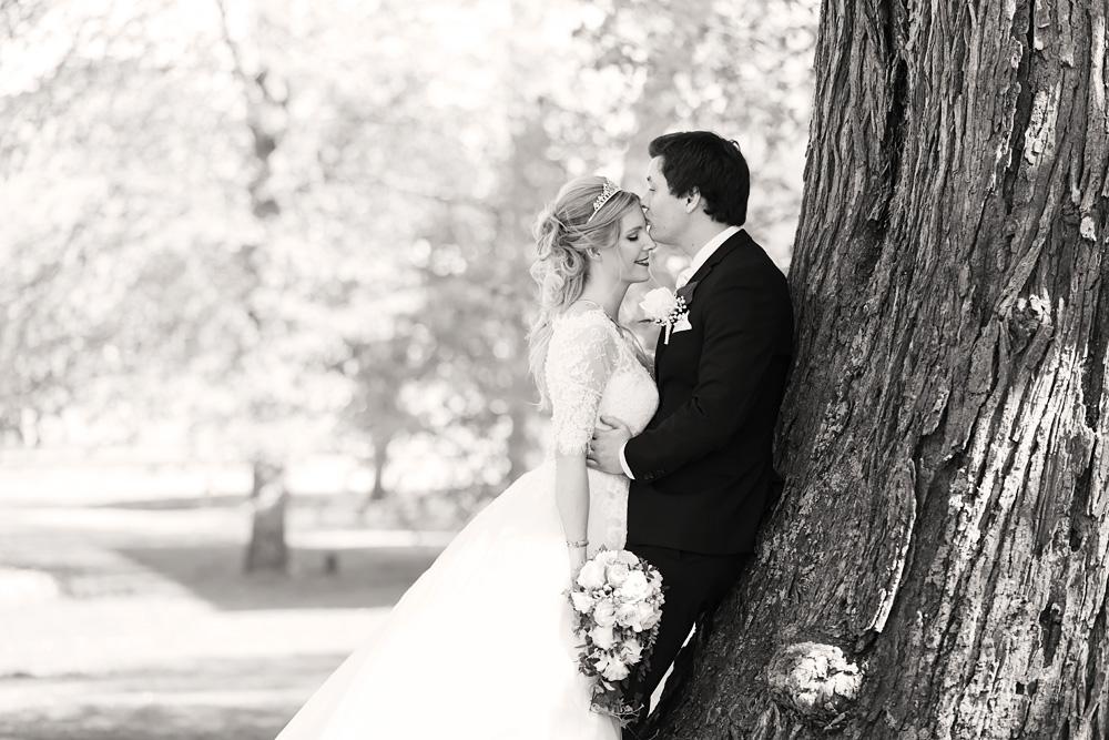 Brudpar vid träd i slottsparken i Kalmar - bröllopsfotograf Phia Bergdahl Västervik