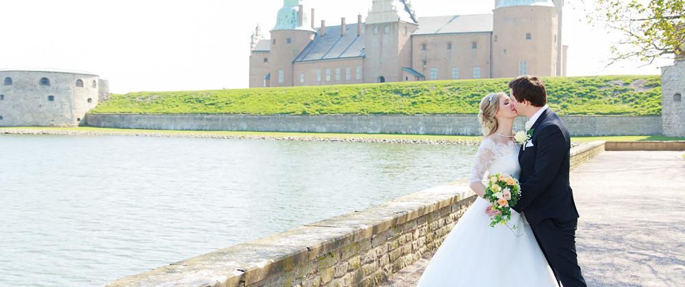 Brudpar som pussas framför Kalmar slott - bröllopsfotograf Phia Bergdahl Västervik