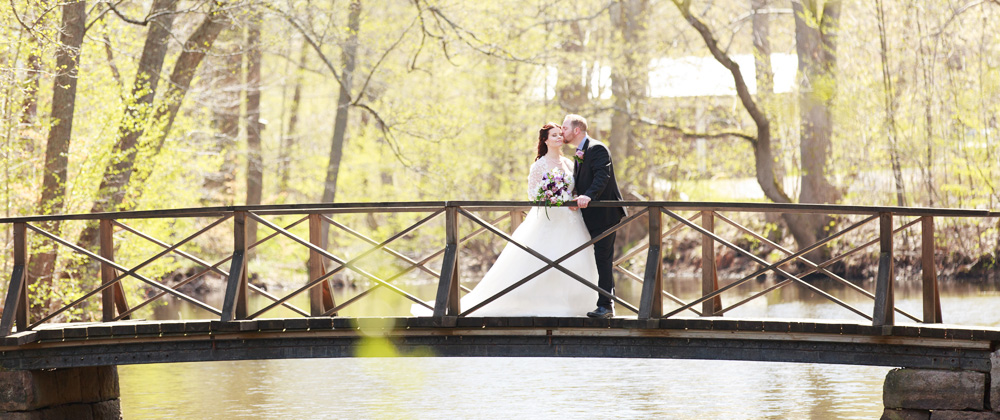 Brudpar på bron i bruksparken i Ankarsrum - bröllopsfotograf Phia Bergdahl Västervik