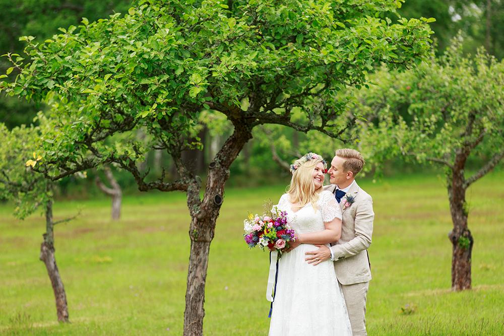 Brudpar i äppellunden, bröllopsfotograf Phia Bergdahl Västervik