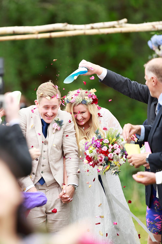 Brudpar får rosblad kastade på sig på bröllop på Kulbacken, bröllopsfotograf Phia Bergdahl Västervik