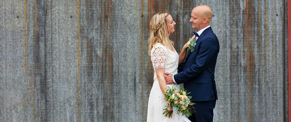 Brudpar framför ruffig vägg - bröllopsfotograf Phia Bergdahl Västervik