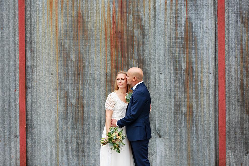 Brudpar framför plåtvägg - bröllopsfotograf Phia Bergdahl Västervik