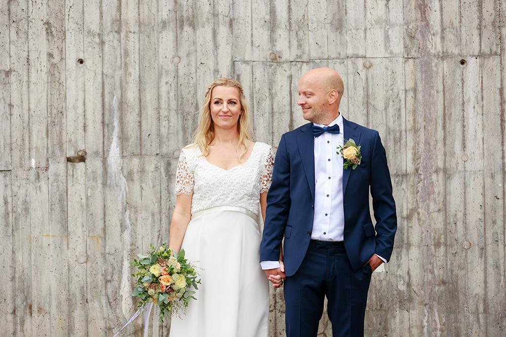 Brudpar framför betongvägg - bröllopsfotograf Phia Bergdahl Västervik