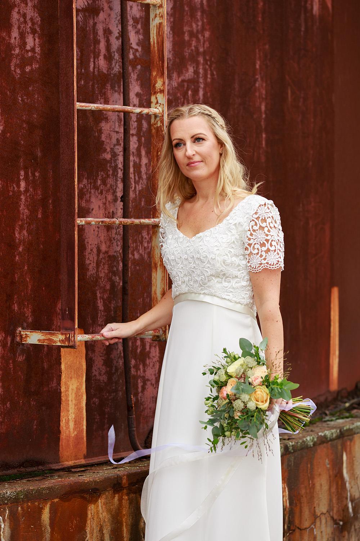 Brud framför rostig cistern - bröllopsfotograf Phia Bergdahl Västervik