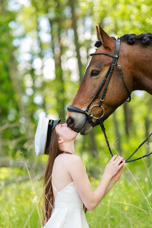 Tjej i studentmössa som pussar häst på mulen