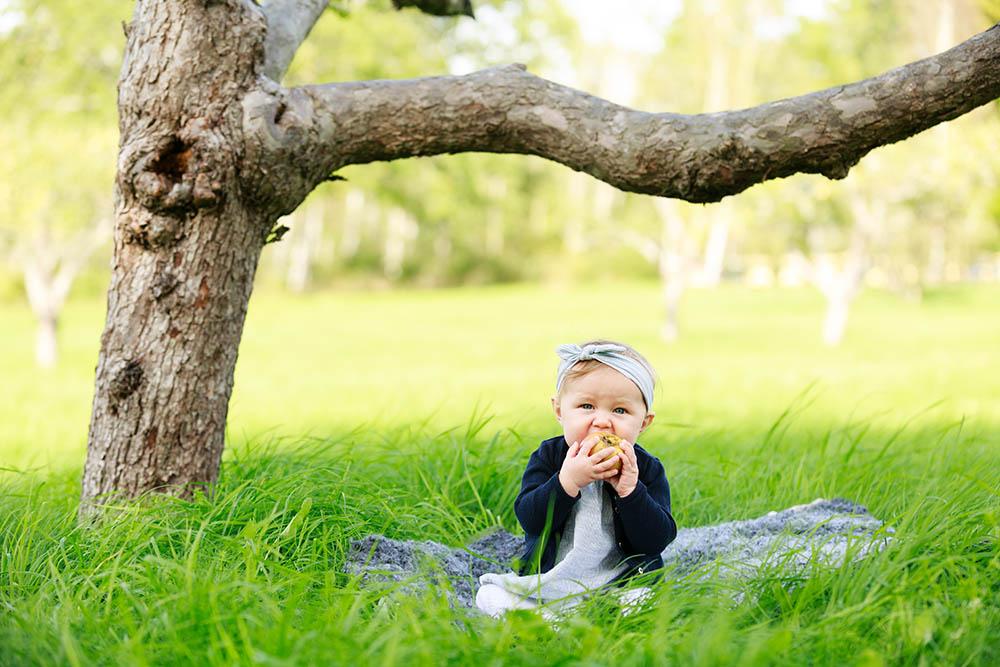 Flicka med blått hårband som sitter i gräset och äter på ett äpple