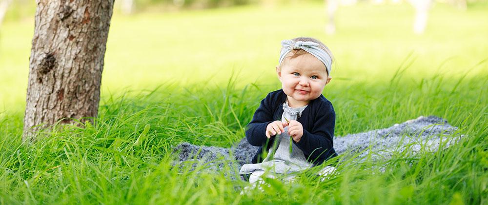 Flicka med blått hårband som sitter på ett fårskinn i gräset