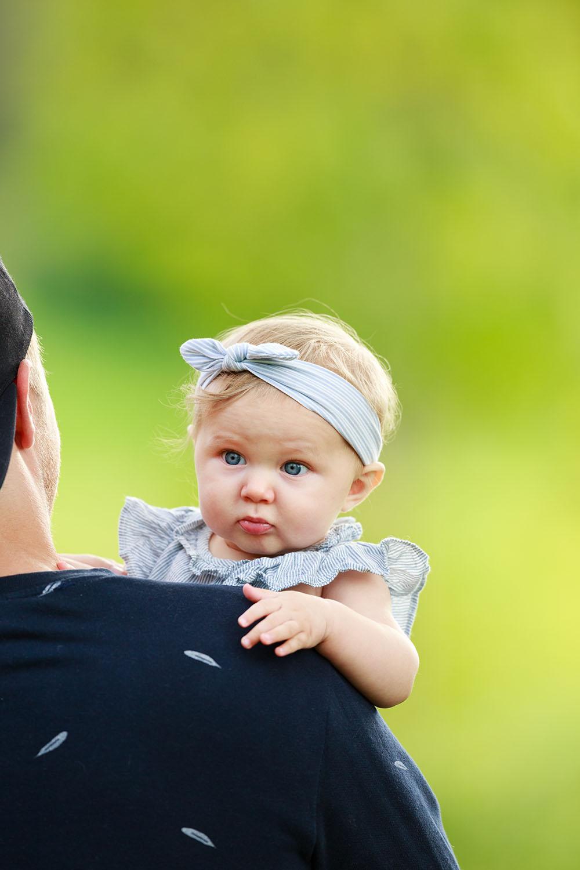 Flicka med blått hårband som sitter över pappas axel