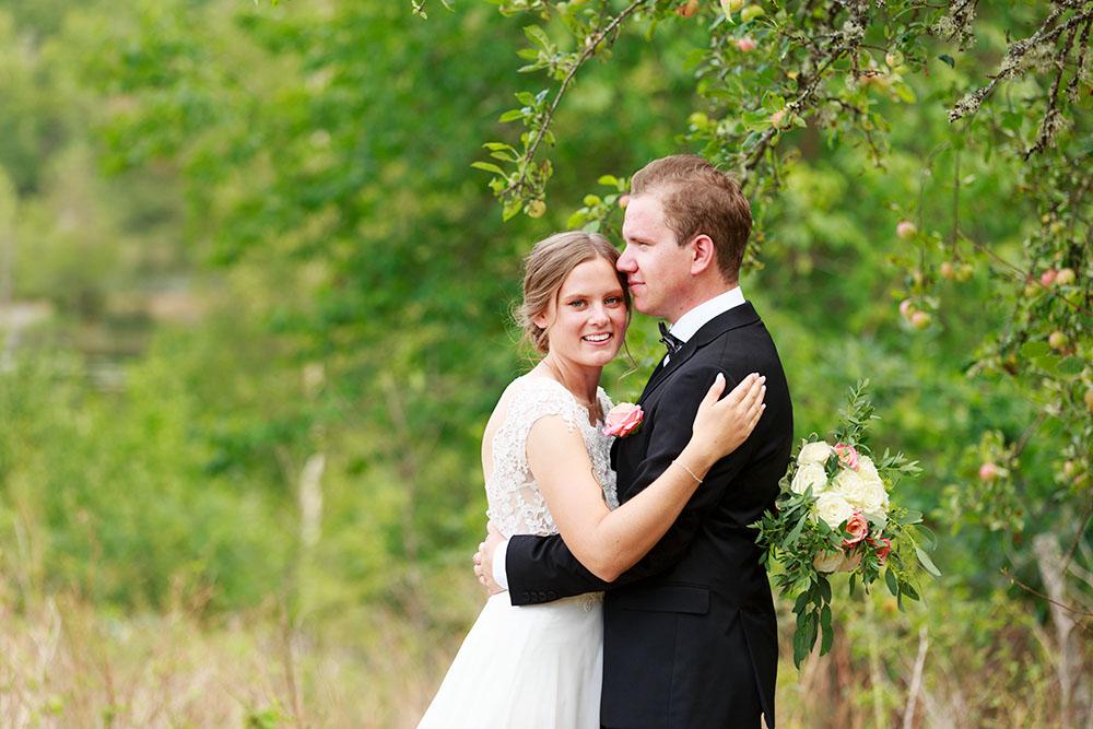 Brudpar utanför Hjorted där de håller om varandra och bruden tittar mot kameran